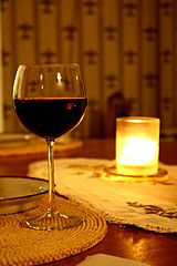 Glass of red wine with a candle