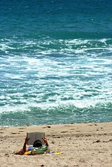 Girl reading book on beach