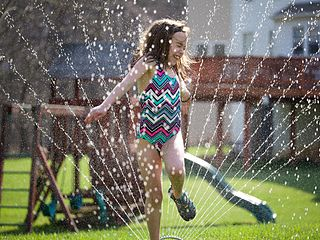 Girl running through sprinklers