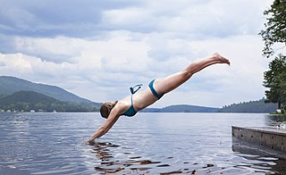Swimmer diving into lake