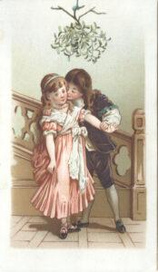 boy kissing girl under the mistletoe